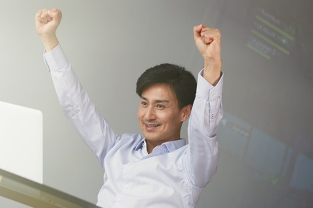 Celebrating success. Excited young Asian businessman arms up while working at office with laptop
