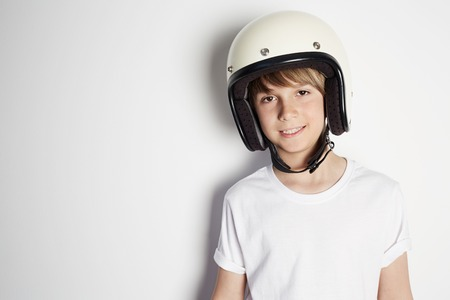 Smiling young cute cheerful teen boy in white tshirt draming to ride a motorcycle isolated on white background