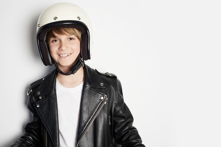 Young happy cheerful teen kid in black leather jacket and white moto helmet smiling on white background 免版税图像
