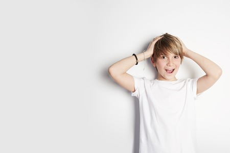 Handsome young boy in white T-shirt posing in front of white empty wall. Concept of children style and fashion. Mock-up.