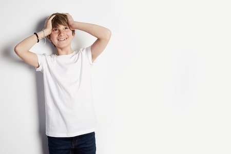 Concept of children style and fashion. Smiling young boy in white T-shirt posing in front of white empty wall background. Mockup