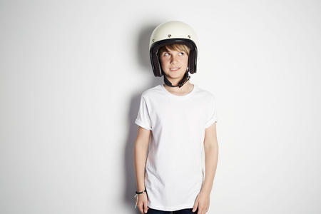 Portrait of young cute cheerful teen boy in white tshirt draming to ride a motorcycle isolated on white background 免版税图像