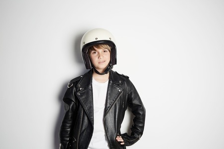 Portrait of Young cool beautiful teen kid in black leather jacket and white moto helmet smiling on white background