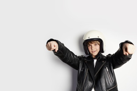 Young cute cheerful teen boy in black leather jacket and white moto helmet pretending to ride a motorcycle over on white background 免版税图像