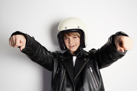 Young stylish kid boy in black leather jacket and white moto helmet pretending to ride a motorcycle over on white background 免版税图像