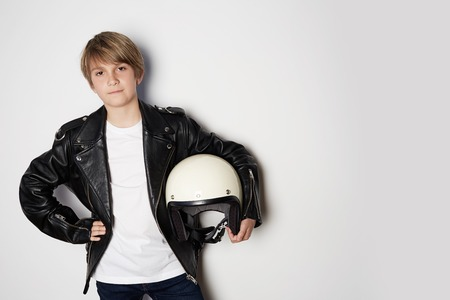 Portrait of Young handsome teen kid in black leather jacket and holding hand white moto helmet smiling on white background 免版税图像