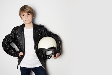 Portrait of Young handsome teen boy in black leather jacket and holding hand white moto helmet smiling on white background