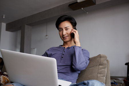 Handsome gay Asian Man using laptop and mobile phone.