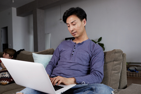 Asian Man Working Laptop Home Connecting Networking Concept. 免版税图像