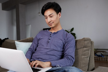 Asian Man Gay Working Laptop Home Connecting Networking Concept.