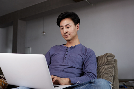 Attractive Asian gay Man Working Laptop Home Connecting Networking Concept. 免版税图像