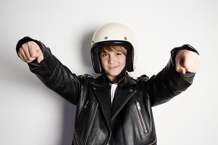 Portrait of young handsome cheerful teen boy in black leather jacket and white moto helmet pretending to ride a motorcycle over on white background 免版税图像