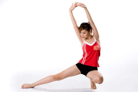 girl in a red tank top with the number 23 doing a squat and arms streching exercise Stock Photo