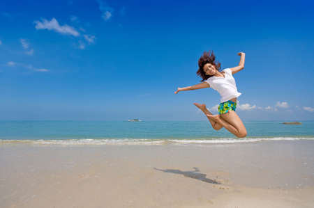 young beautiful girl jump gracefully at the beach photo
