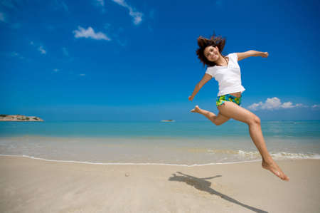 young beautiful girl jumping happily at the beach photo