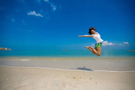 ecstatic: young beautiful girl jumping happily at the beach Stock Photo