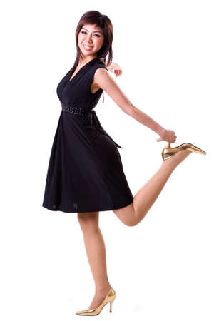 Young Carefree Woman In Black Dress And Gold Heels Isolated On