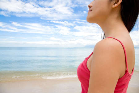 a red top woman look ahead towards the sea by the beach with blue cloudy sky photo