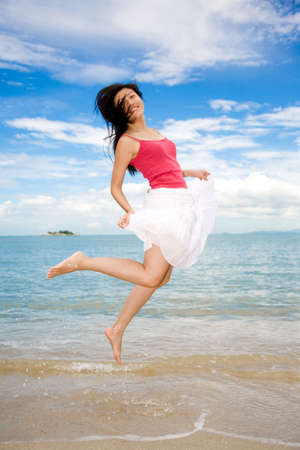 girl jumping happily by the seashore with the blue sky background photo