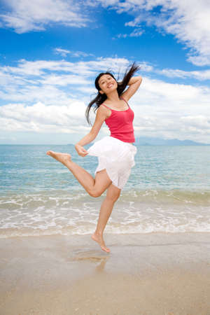 girl jumping happily with one hand holding hair by the beach and blue sky photo