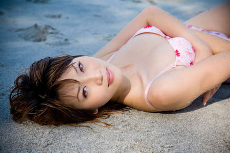 gracefully: woman lying on the beach smile gracefully Stock Photo