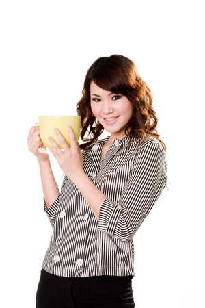 downtime: young woman holding a big green cup with both hands smiling Stock Photo