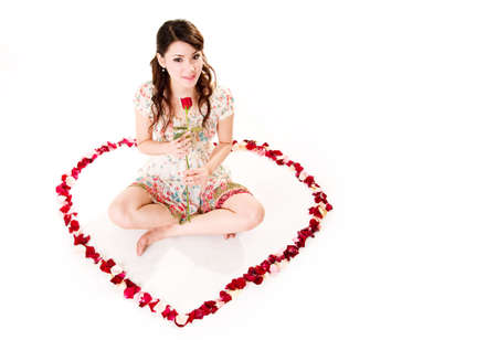 young woman with roses sitting inside a rose petal heart shape photo