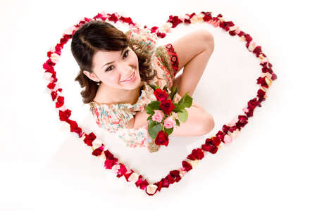 young woman with roses sitting inside a heart shaped made of rose petals photo