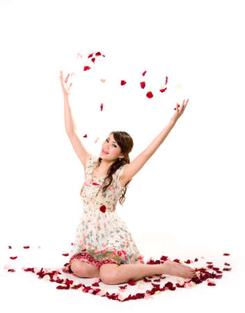 a very happy and joyfull girl tossing rose petals in the air photo