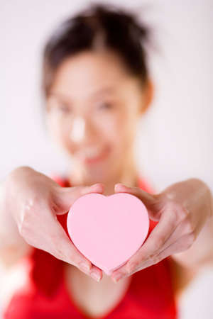 lady presenting  heart shape box of valentine gift with gift in focus and person out of focus Stock Photo