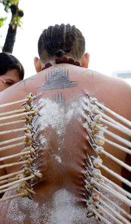 beliefs: a devotee of thaipusam with hooks pierce through their backs in their beliefs Stock Photo