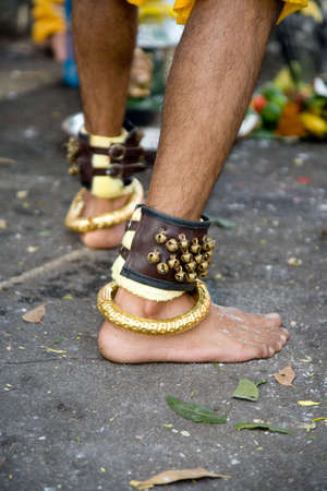 hindus: thaipusam devotee wearing a bracelet of bells and gold
