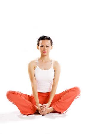 cross leg: mujer joven que sienta la pierna cruzada en una actitud del ejercicio que relaja que mira fijamente la c�mara fotogr�fica
