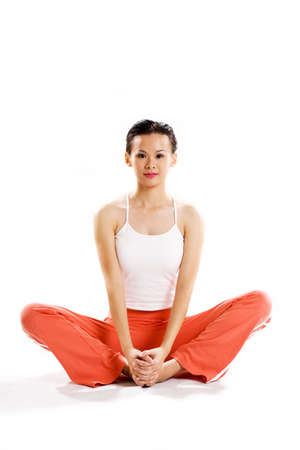 cross leg: young woman sitting cross leg in a relaxing exercise pose staring at camera Stock Photo