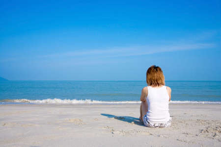 young woman sitting lonely by the beach facing the sea with blue sky Stock Photo - 2455024