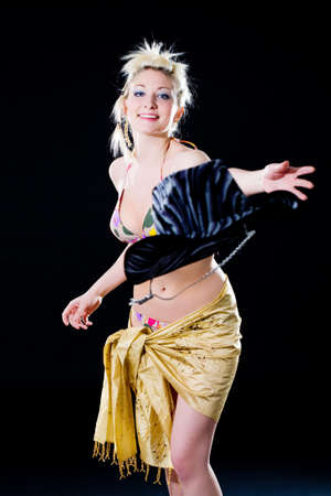 woman throwing a cowboy hat happily with gold scraf wraping her hips photo