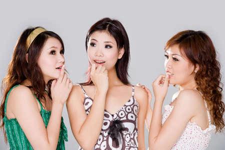 gossip: groep vriendinnen met nieuwsgierigheid gezicht roddelen Stockfoto