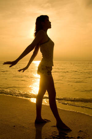 golden silhouette of a woman doing yoga exercise at sunset  photo