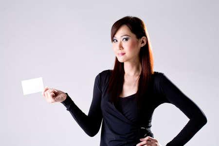 businesswoman card: Young Professional woman holding and showing a white Card while  smiling Stock Photo