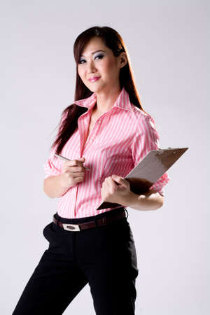 promotion girl: pink shirt businesswoman holding a writing pad and smiling Stock Photo