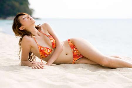 sun bathing: sun bathing woman in orange floral bikini Stock Photo