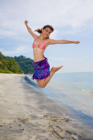 young woman jumping happilly at the beach