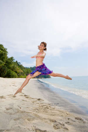 young woman jumping happilly at the beach photo