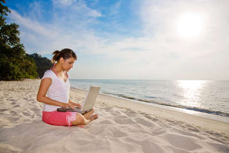 young woman working on her laptop on a beautiful beach