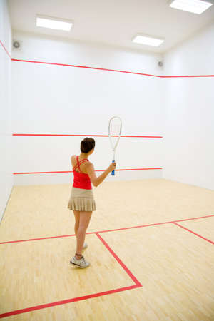 woman playing squash in the squash court