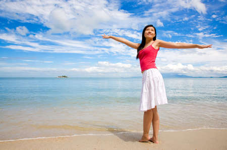 woman streching out arms relaxing by the beach photo