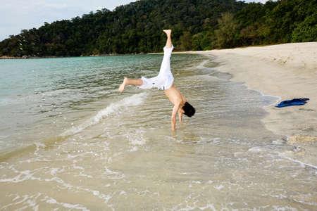 man doing cartwheel by he beach photo