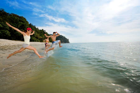a group of boy and girl friends jumping into sea excitedly