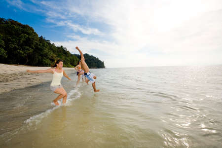 a group of friends having fun by the beach jump into the sea Stock Photo - 2640778