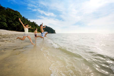 happy friends having fun by the beach jumping into the sea Stock Photo - 2640826